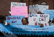 """Members of Picture the Homeless protest outside councilwoman's office with signs that read """"Organizing for Justice and Respect"""" and """"We Need Housing, not Warehousing."""""""
