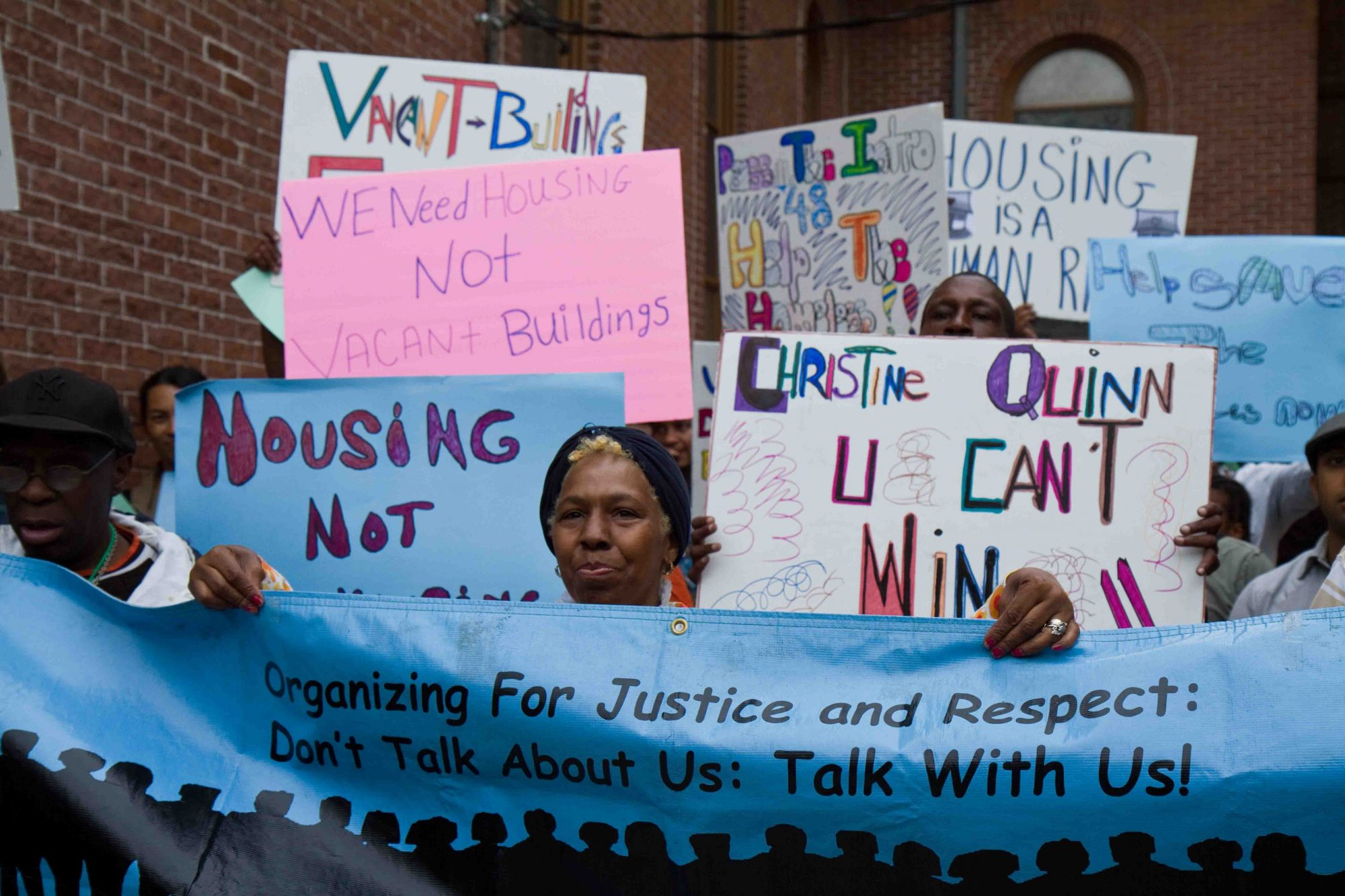 """Homeless organizers protest outside councilwoman's office with signs that read """"Organizing for Justice and Respect"""" and """"We Need Housing, not Warehousing."""""""