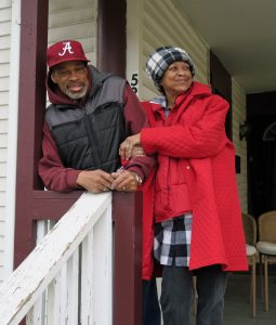 An African-American man and woman stand happily outside on their front porch. The woman is wearing a red coat and a black and white hate, while the man is reader a read Oakland A's hat and a black jacket.