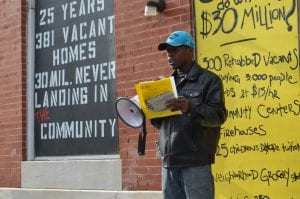 """An African-American man speak through a bullhorn in front of a building with wording on it. The wording says """"25 years, 381 vacant homes, 30 million never landing in the community."""""""
