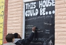 """A man and a woman stand in front of a chalkboard sign that reads """"This House Could Be ...""""The man is writing on the board, as many others have done. Some of the suggestions for what the house could be include a community gathering space and a senior center."""