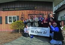 """A group of residents stand outside of the Oak Hill Meeting House holding a sign that reads """"We Own It."""" They are clapping and cheering."""