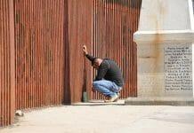 man at border fence