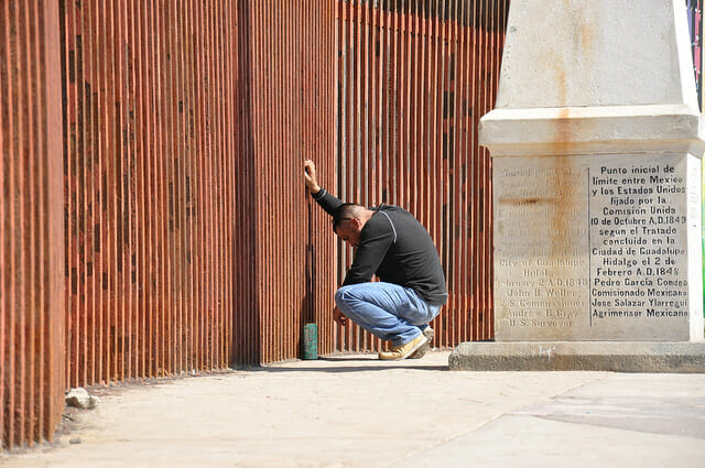 A man at border fence where family separation is taking place.