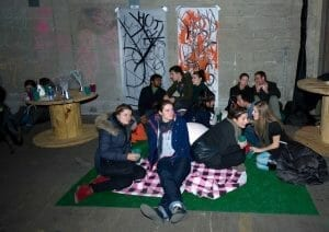 people on floor with picnic blankets.