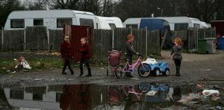 Children play on an Irish Traveller site on Dale Farm in 2011. A young boy with glasses rubs his eyes outside in Dale Farm, which was once the site of the largest Irish Traveller concentration until families were evicted in 2011. A health impact assessment helped house this indigenous group.