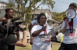 Kennetha Patterson of Homes for All in Nashville speaks on a megaphone during Renter's Week of Action.