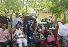 North Minneapolis tenants pose together with their fists in the air during a barbecue
