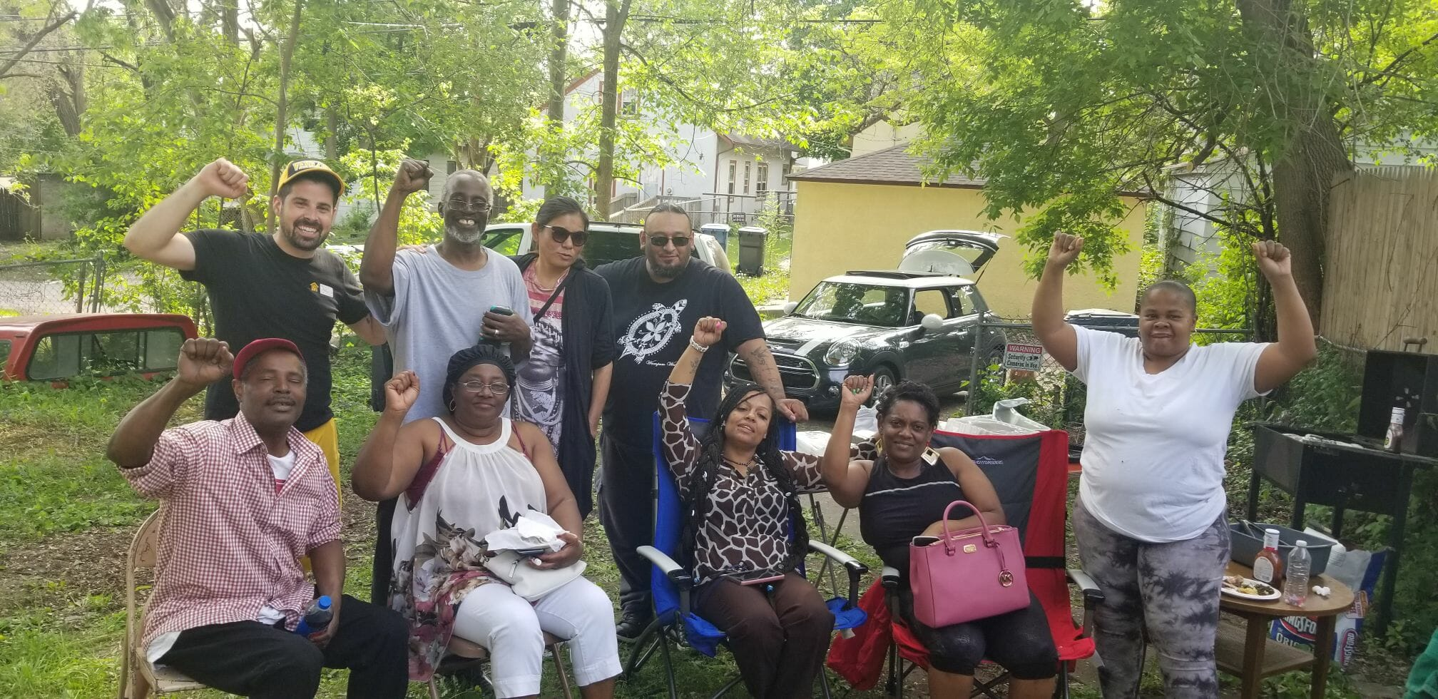 North Minneapolis tenants pose together with their fists in the air during a barbecue. The tenants are facing eviction.