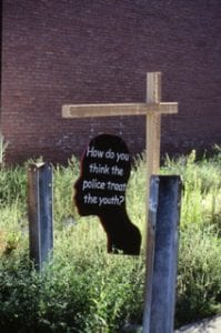 A temporary hanging sign in the shape of participants' silhouettes was public art in one neighborhood.