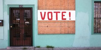 vote sign on boarded window