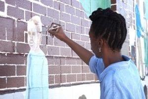 An African American mural artist paints on a brick facade.