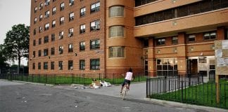 A child rides her bike outside of Ocean Bay (Bayside) Apartments in Far Rockaway, the first housing project in New York City to take part in the RAD program, as well as the largest RAD-funded project in the country.