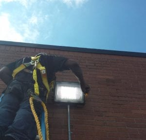 A OWN Rochester member installs an LED lighting fixture. The nonprofit leverages the community's resources—the collective purchasing power of anchor institutions, the intellectual and human capacity of residents, and the financial resources of philanthropy—to aggregate institutional demand and provide support to worker-cooperative businesses.