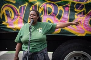 An Oakland activist speaks to local residents about a market-rate development that is slated for a vacant lot in the city.