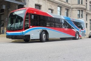 A blue, red, white, and gray bus. The cost of a bus ride is a pretty good deal for a penny-conscious nonprofit business traveler, but conferences tend not to include information about bus routes.