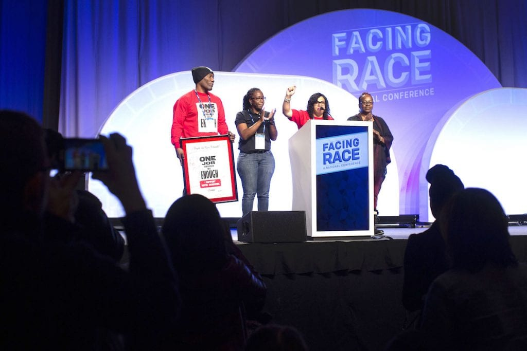 Four people on a stage during the Facing Race conference, which in 2018 negotiated a community benefits agreement with local leaders.