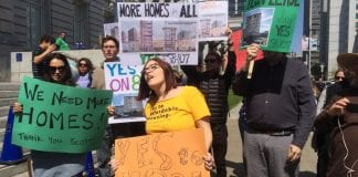 """Laura Foote (in yellow shirt at center) at a counter-protest to a rally opposing statewide upzoning bill SB 827. She's surrounded by fellow protestors who are holding signs that read """"We Need More HOmes"""" and """"More Homes for All."""""""