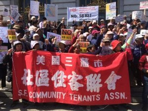Members of the San Francisco Community Tenants Association hold a large red resign during a rally against SB 827.