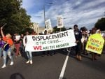 """Boston residents participants marched to a nearby national gathering of YIMBYs with a sign that reads """"Displacement is the Crisis ... We Are The Answer."""""""