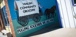"""A painting that reads """"Walsh Community Grocery: Pulling Together We All Win."""""""