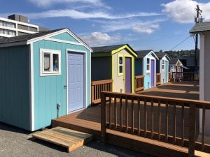 Six tiny houses share a common deck.