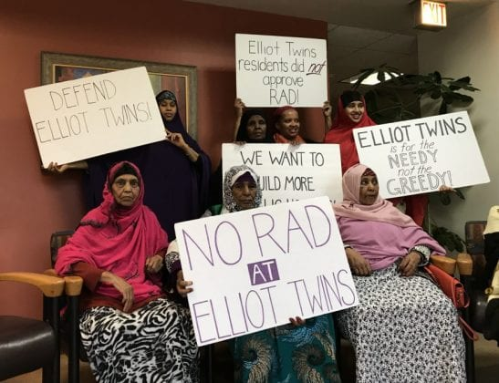 """Women hold up signs that read """"No RAD at Elliot Twins"""" and others."""