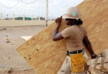 Woman construction worker carrying wood