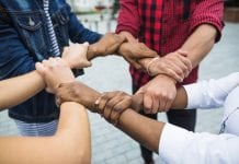 four people linking hands together