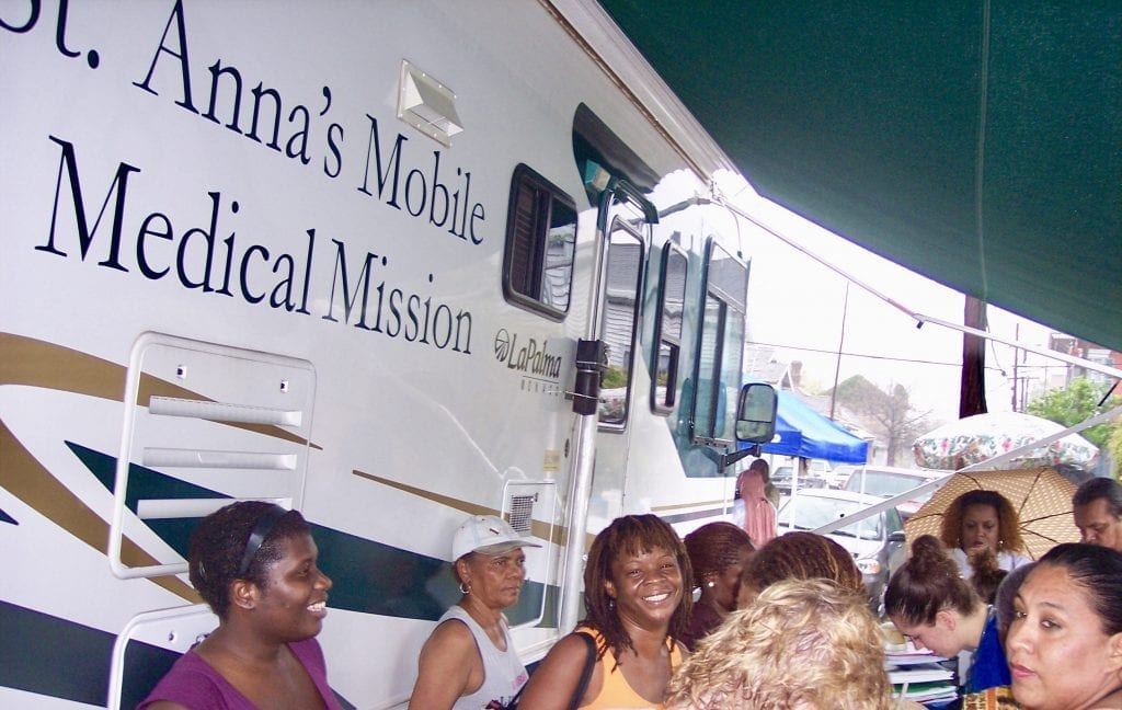 Residents stand if front of St. Anna's medical RV.
