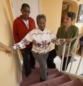 Two women help a senior go up the stairs to her home. Like Project Sustained Legacy, the CAPABLE program helps seniors age in place.