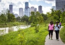 Parks can be a key component of building resilience. Two women walk adjacent to Buffalo Bayou Park in downtown Houston, Texas.