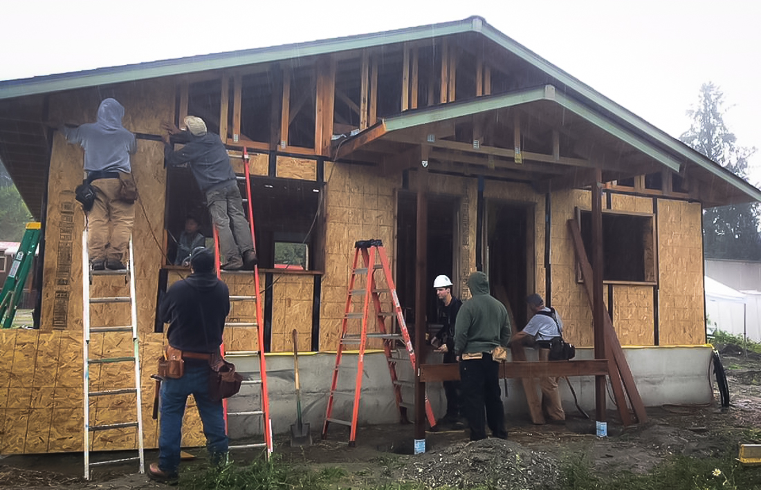 People work to build a home using an approach to create a passive house.