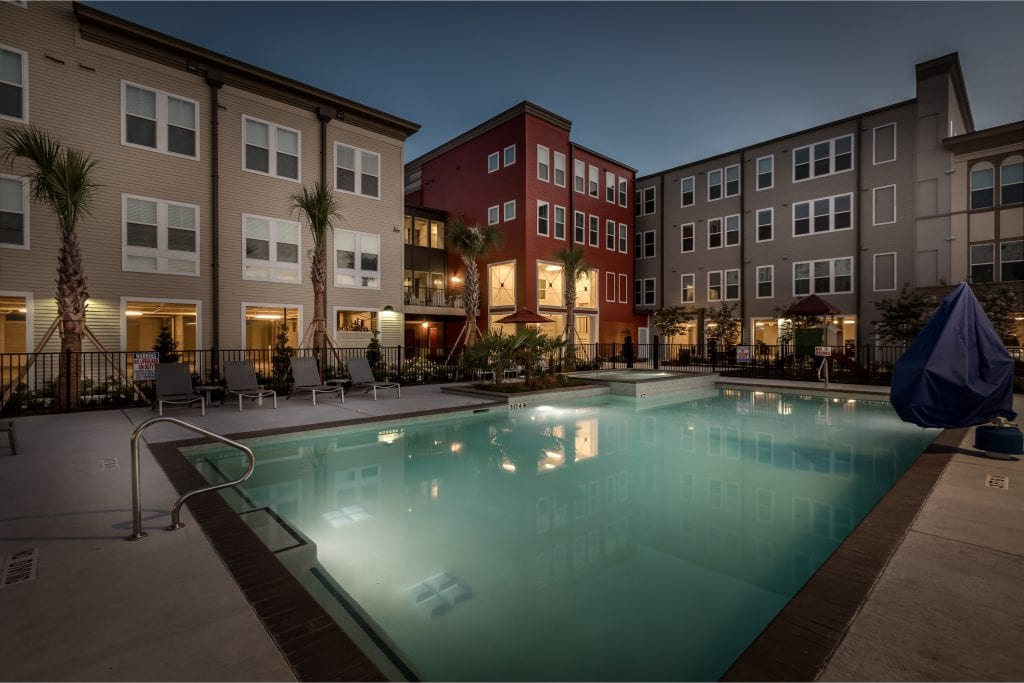 A pool sits in front of three large buildings are part of the Villas on the Strand housing complex.