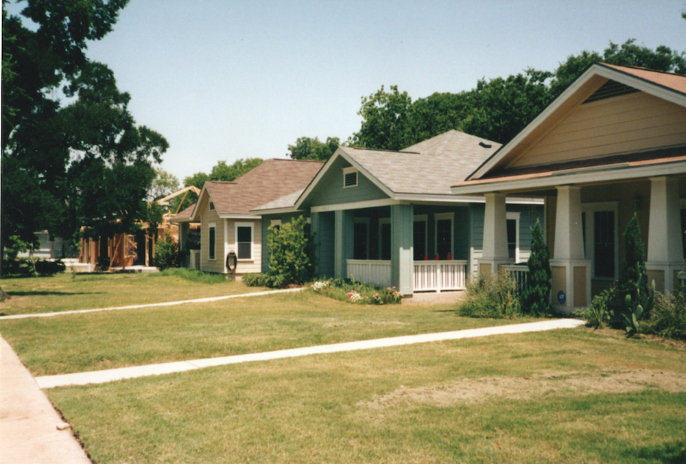 A row of homes to the right with lawns in front. These homes are located in the Guadalupe neighborhood in Austin, Texas, were a community preference policy gives residents with historic ties to the neighborhood receive priority for affordable housing.