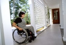 woman in wheelchair approaches door of house