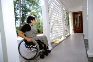 a woman with disabilities approaches the door of a house while in a wheelchair