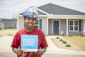 affordable housing woman in hard hat as part of the cost of home campaign.