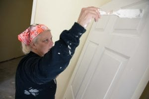 A woman paints a door white as part of the Self-Help Housing Program.