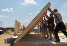 A group works to raise a wall as part of the Self-Help Housing Program.