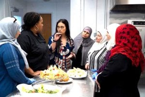 As part of a CultureBank Dallas initiative, a group of women speak with one another while eating.