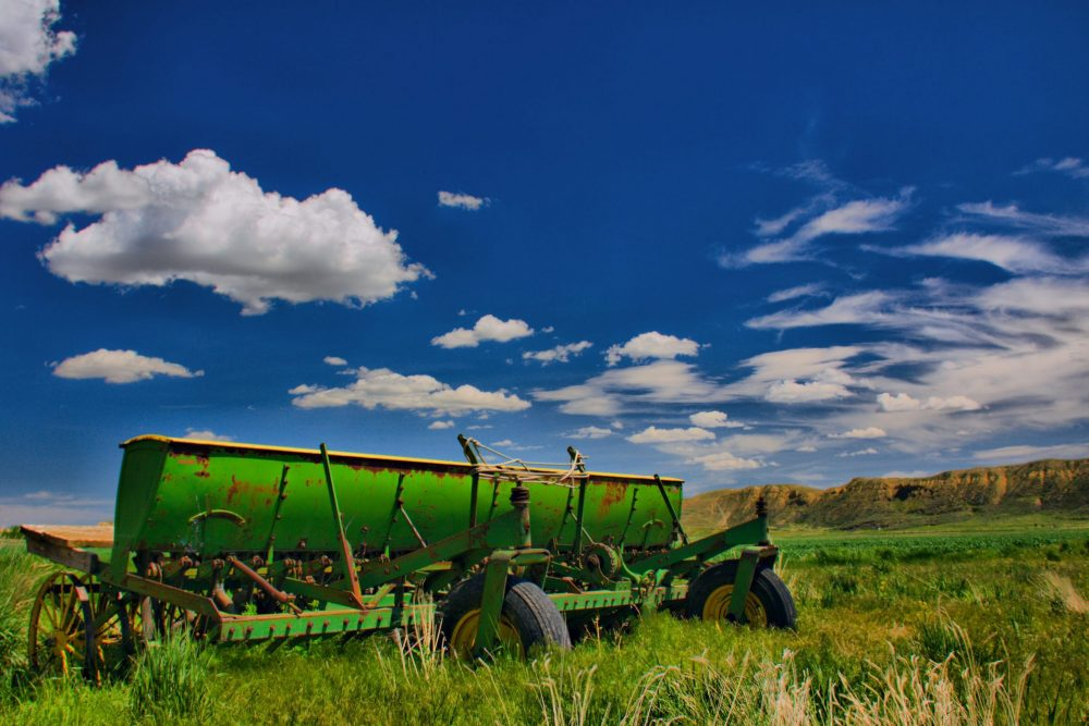 Farm equipment on grass in Montana, with a blue sky with puffy white clouds.