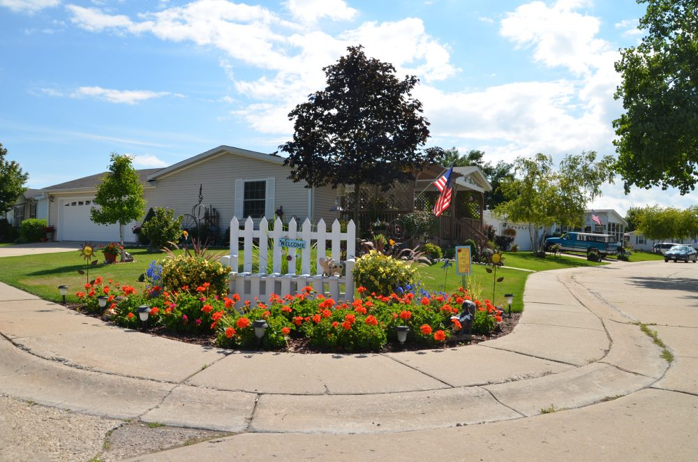 """A small white fense with a sign that reads """"welcome"""" and red flowers frame a resident-owned community in Wisconsin."""