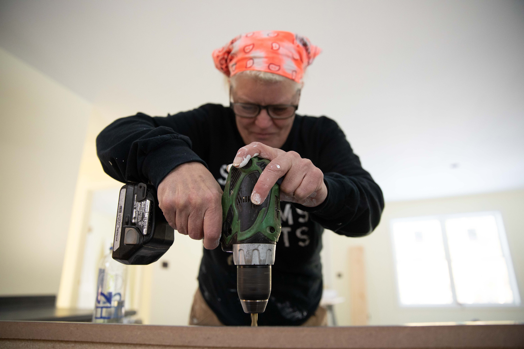 As part of a self-help housing program, a Main woman uses an electric screwdriver to build her home.