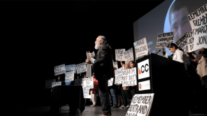 As part of a CultureBank Dallas program, people are on theatre stage with signs as part of a performance.