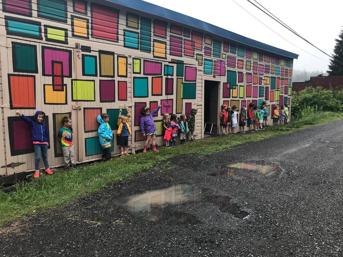 Kids stand in front of a mural in Thomas, West Virginia.