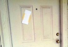 Eviction notice: door with envelope taped to it