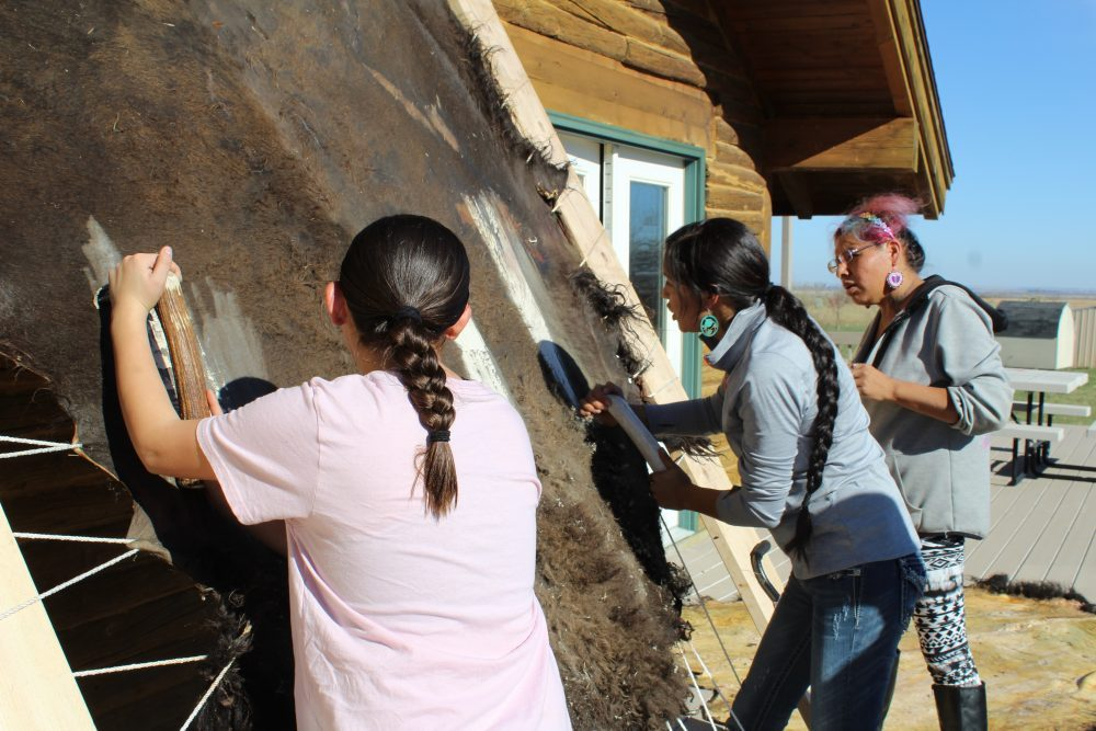 Native students tanning hide as part of a program called Indigenous Visionaries