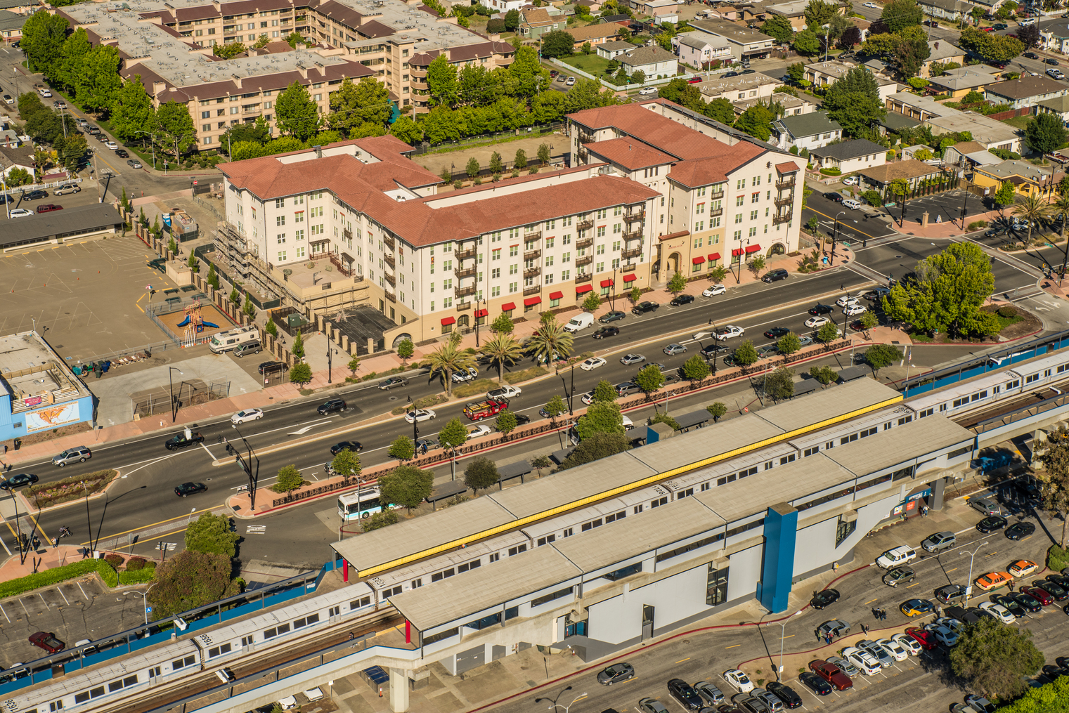 A 200 unit building was built on transit land in California. In front of the building is the San Leandro Bart Station.