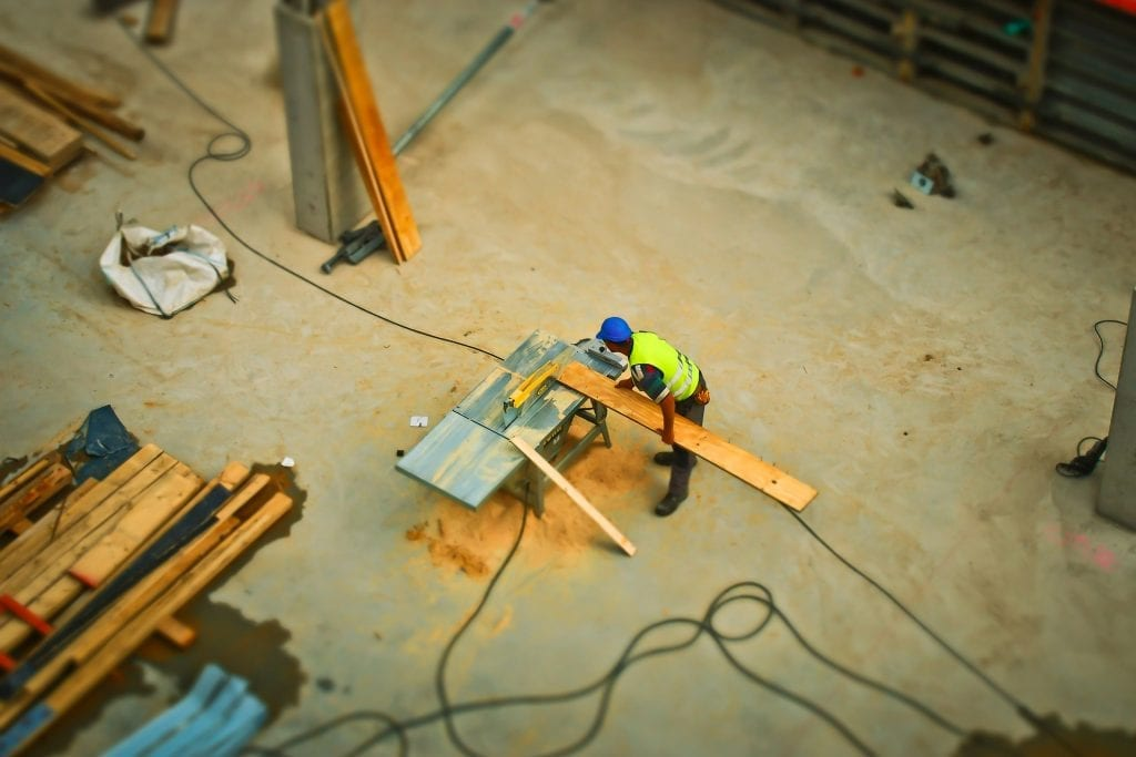 An aerial view of construction worker sawing board, an image shown to reflect community development funding for communities.